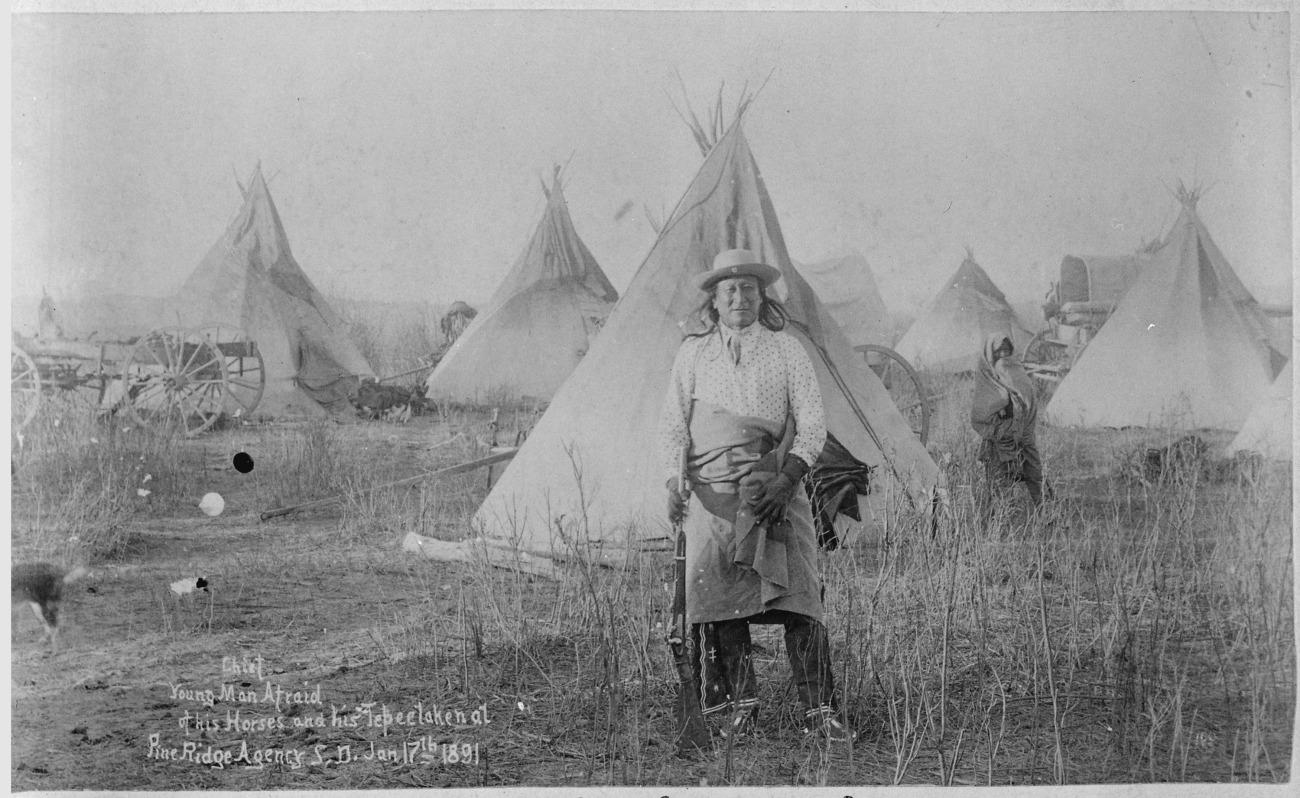 Young-Man-Afraid-of-His-Horses_(Tashun-Kakokipa),_an_Oglala_Sioux,_standing_in_front_of_his_lodge,_Pine_Ridge,_South_Dak_-_NARA_-_530813